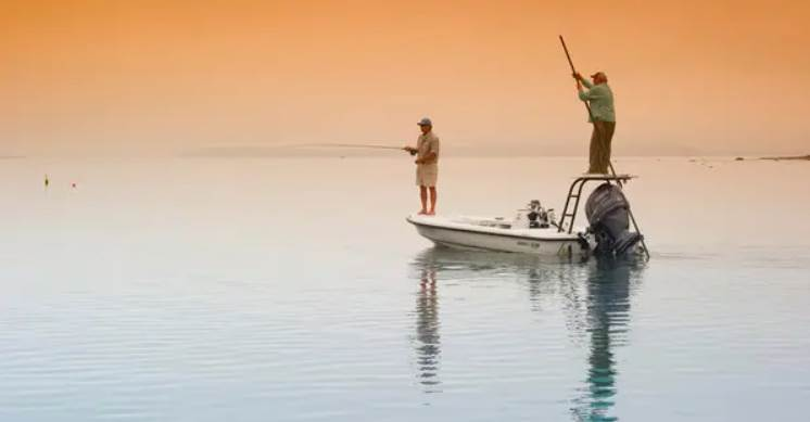 image of two persons fishing in a boat