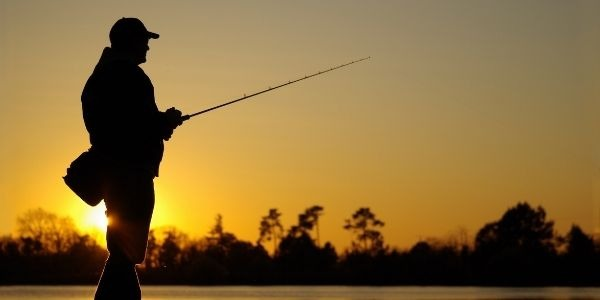 image of a person fishing in sunset