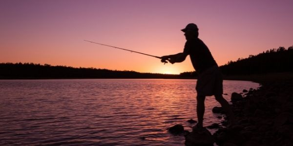 image of a person fishing in the dawn
