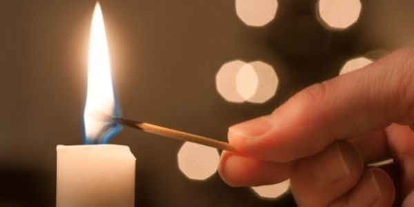 image of a person lighting the candle