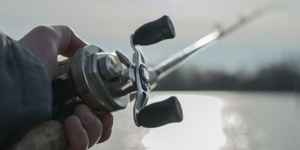 Image of a person holding the baitcasting reel