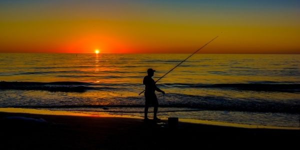 Image of a person surf fishing in dusk