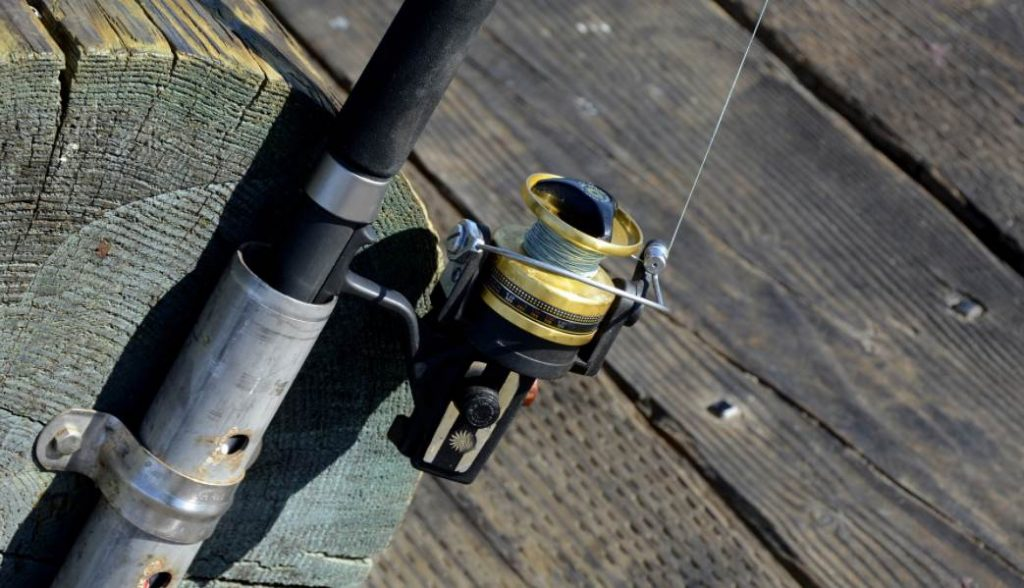 image of a fishing rod attached to a piece of wood